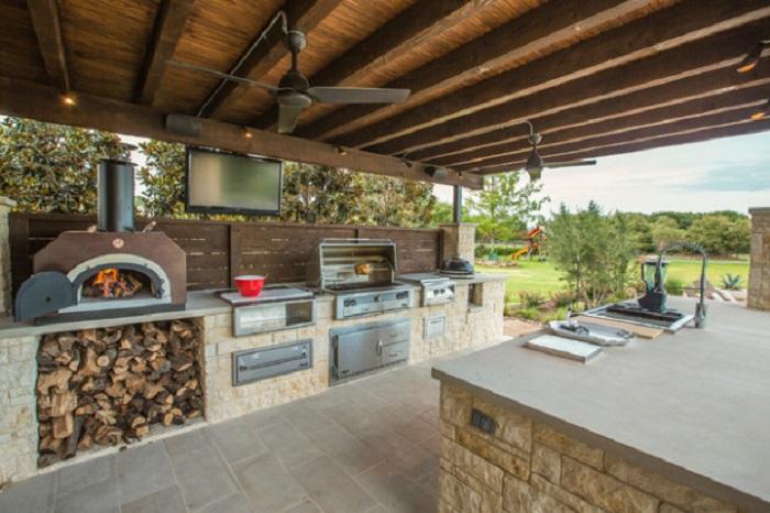 Просторная летняя кухня, скрытая от посторонних глаз камуфляжной сеткой, с зоной для барбекю, рабочей зоной и зоной для хранения продуктов.