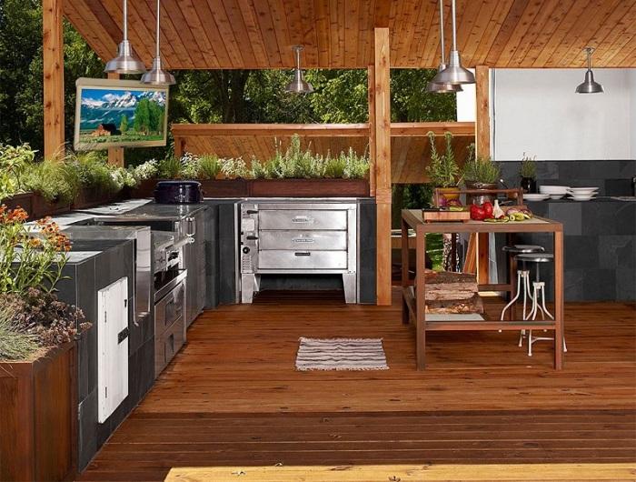 Современная летняя кухня в частном доме, расположенная на просторной террасе – отличное решение, которое избавит вас от дополнительной пристройки.