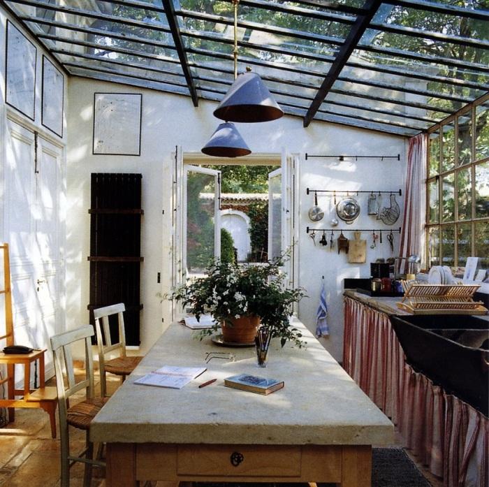 Простое местечко для отдыха с обычным столиком и деревянными стульями, которое не потеряло своего неповторимого очарования летней кухни.