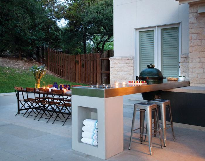 Стильная и аккуратная площадка для отдыха, вымощенная тротуарной плиткой, с классическим столом и стульями, зоной для барбекю и барной стойкой.