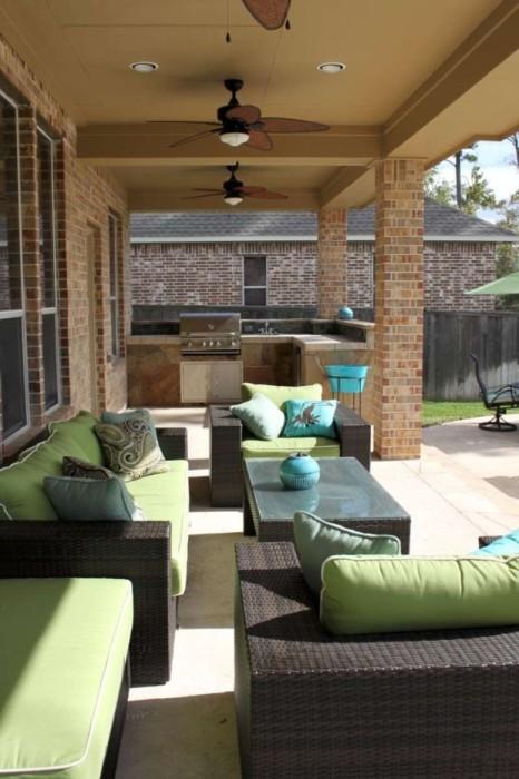Летняя кухня с верандой, обустроенная на заднем дворе, с просторными комфортабельными диванчиками, небольшим журнальным столиком и традиционным кухонным островком.