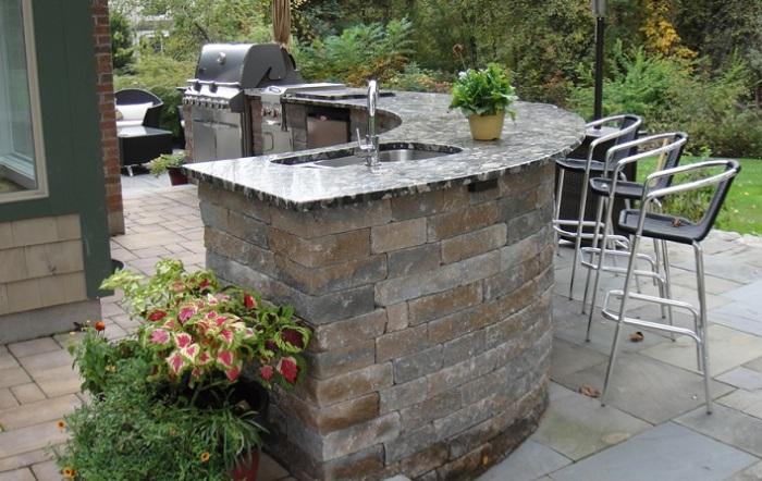 Летняя кухня на дачном участке, в которой преобладают каменные элементы, устойчивые к неожиданным капризам погоды.