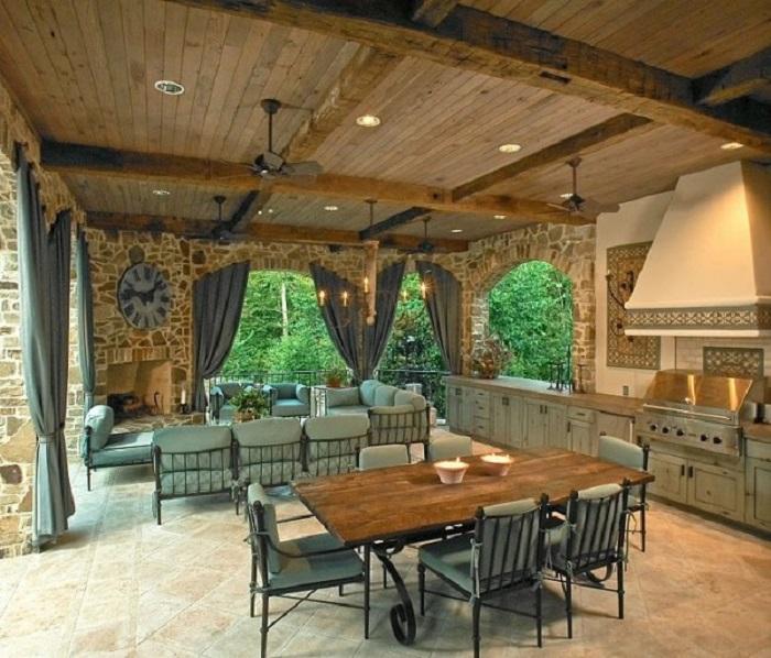 Просторная летняя кухня, облицованная натуральным камнем, с несколькими секциями для отдыха.