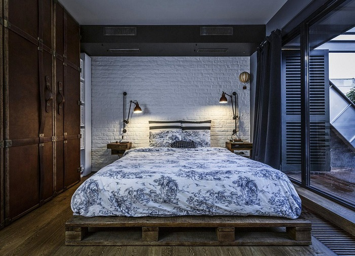 Кровать из деревянных поддонов и отреставрированный старинный шкаф органично дополняют индустриальный стиль спальной комнаты.