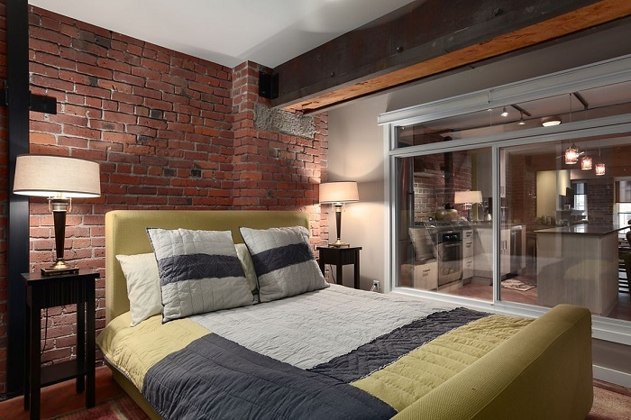 Кирпичная кладка, строгие светильники и вентиляционная шахта, оставленная на виду - характерные элементы для спальни в стиле лофт.