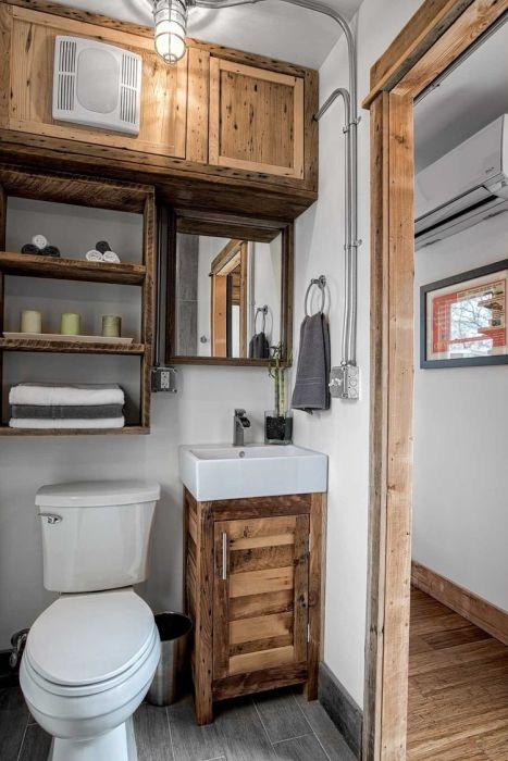 Благодаря деревянным элементам ванная комната смотрится особенно уютно.