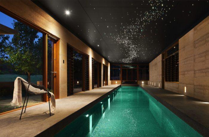 Узкий плавательный бассейн длиной более десяти метров, который расположен в пристроенном к дому помещении.