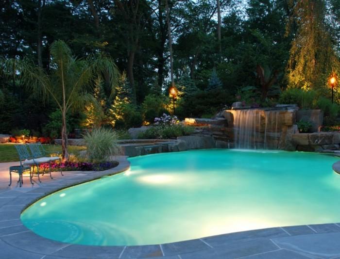 Плавательный бассейн оригинальной формы с необычным фонтаном и яркой подсветкой дна.