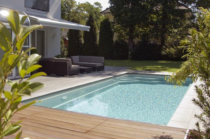 Неглубокий каркасный бассейн прямоугольной формы на заднем дворе.