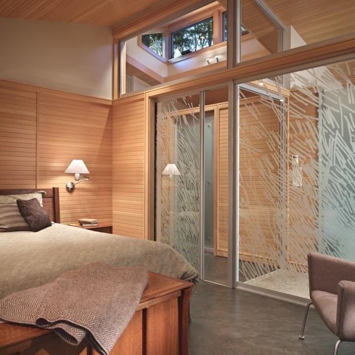 Стеклянная стена в интерьере спальной комнаты - оригинальное и современное решение.