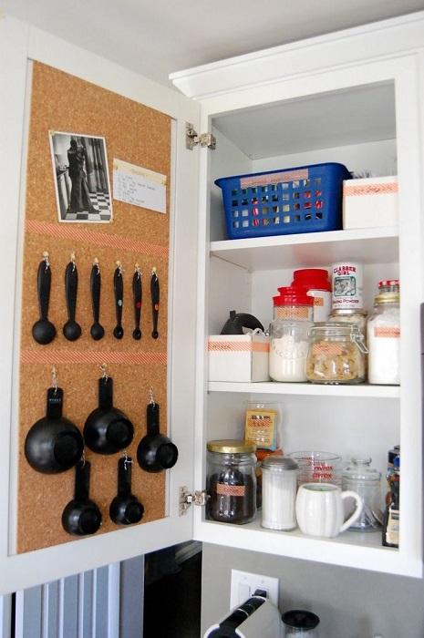 Дверцы шкафчиков можно использовать рационально, прикрепив к ним крючки и вешая на них мерную посуду.