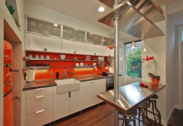 Яркий фартук насыщенного оранжевого цвета станет ключевым элементом в интерьере маленькой кухни.
