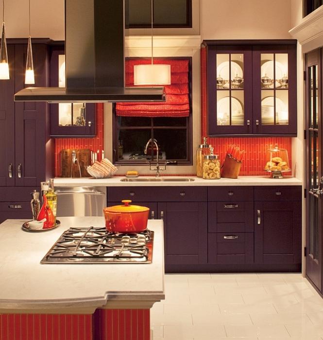 Контрастное сочетание ярко-оранжевого фартука с мебелью матового фиолетового цвета.