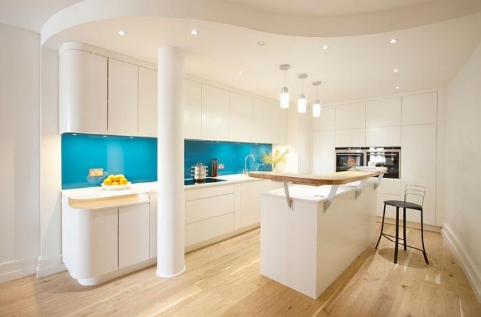 Безупречное сочетание - белая кухонная мебель с фартуком из стеклянных панелей яркого бирюзового цвета.