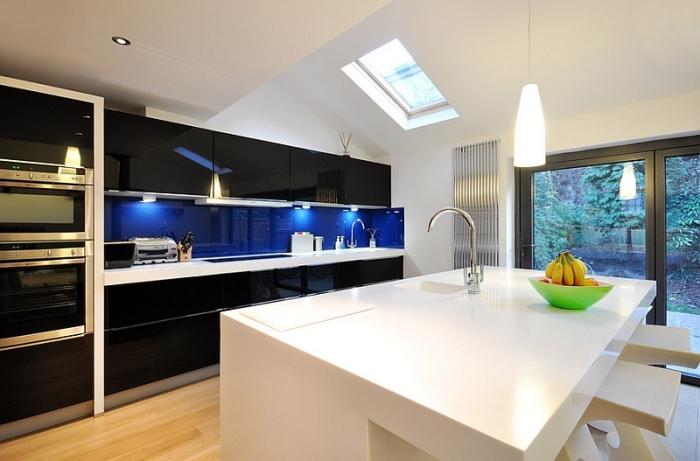 Мебель с черной глянцевой поверхностью эффектно сочетается со стеклянным фартуком насыщенного синего цвета.
