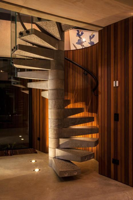 Компактная спиральная лестница с металлическими перилами и ступенями из гранита - настоящая изюминка в интерьере.
