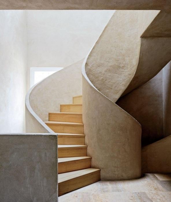 Винтажная лестница с деревянными ступеньками с монолитными бетонными перилами.