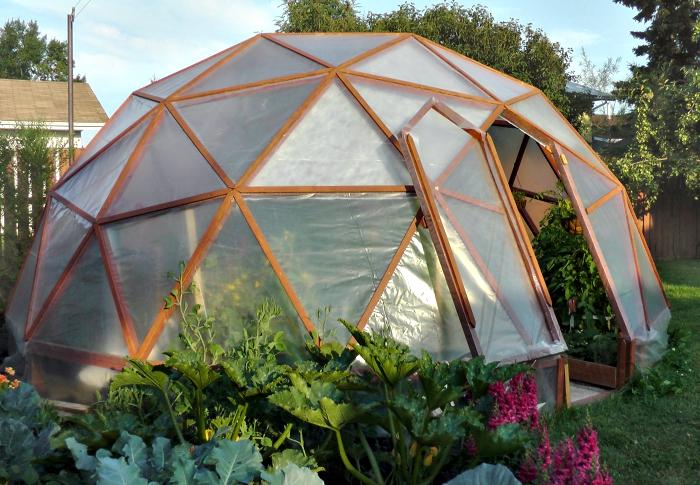 Небольшая многоугольная теплица, каркас которой построен из натуральной древесины и покрыт обычной полиэтиленовой клеенкой.