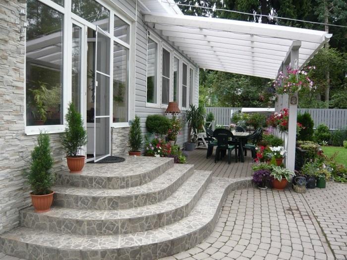 Летняя веранда с элементами в стиле прованс, пристроенная к одноэтажному загородному домику.
