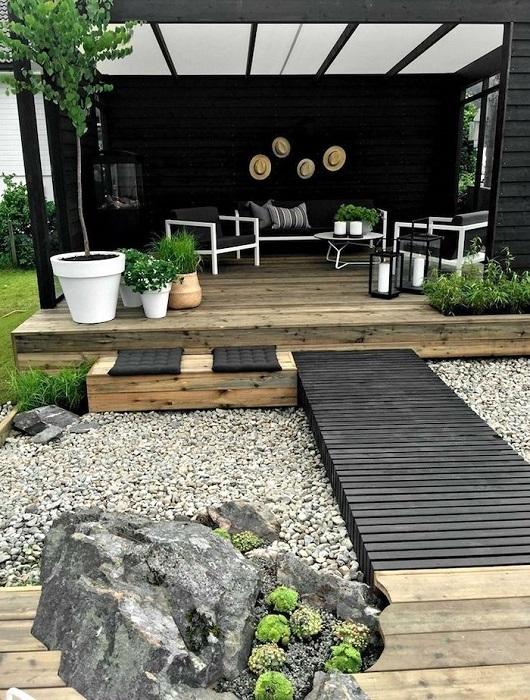Великолепная деревянная площадка для отдыха с компактной современной мебелью, напольными светильниками и контрастными белыми кашпо.