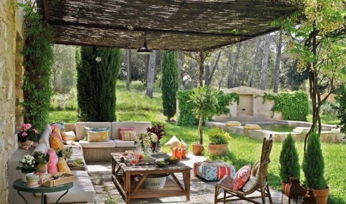 Небольшой задний двор, вымощенный традиционной тротуарной плиткой, с небольшим журнальным столиком и удобными диванчиками.