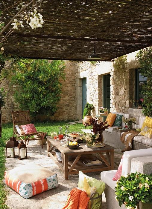 Терраса, оформленная в ярких тонах, с угловым диваном и обеденным столиком.