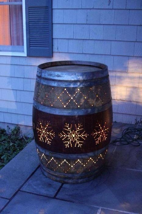 Старая бочка в виде светильника может стать настоящим украшением для садового участка.