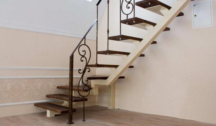 Лестница из тёмного дерева с коваными односторонними перилами.