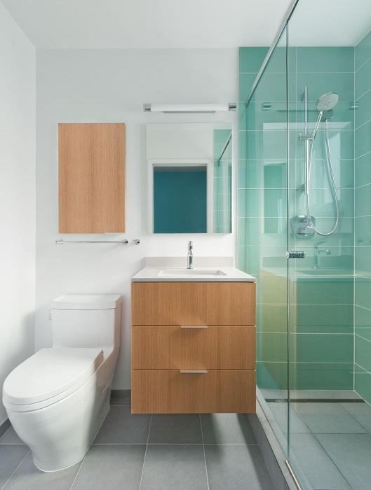 Эргономичная планировка и оригинальная комбинация светлого и бирюзового оттенка в интерьере ванной комнаты.