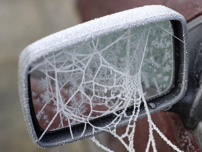 Зеркало заднего вида, опутанное ледяной паутиной.