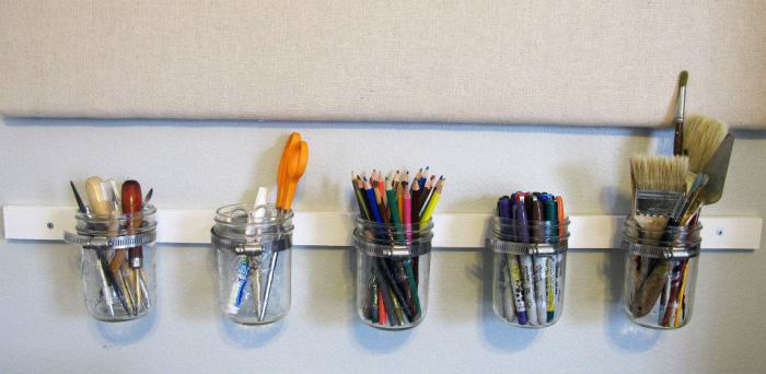 Банки, прикрепленные к деревянному бруску, для хранения ручек и карандашей.