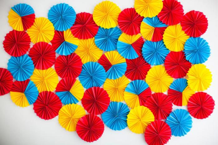 Небольшие гофрированные цветочки в качестве украшения на стену.