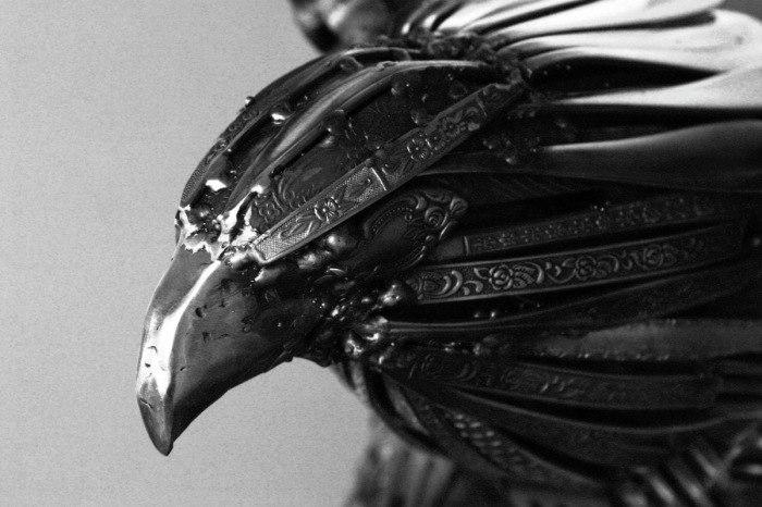 Суровый взгляд орла из ручек от столовых приборов из нержавеющей стали.
