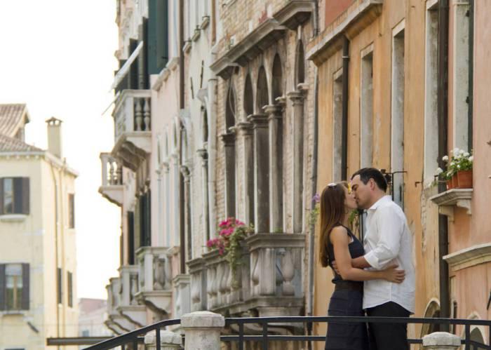Пара, целующаяся на балконе старинного дома.