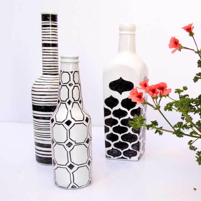 Бутылки, выкрашенные в белый цвет и украшенные маркером, в качестве ваз для цветов.