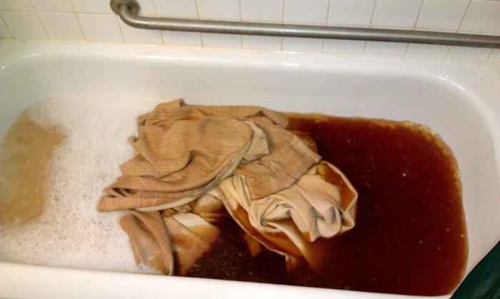 Темная вода, которая вытекает во время стирки занавески из комнаты курильщиков.