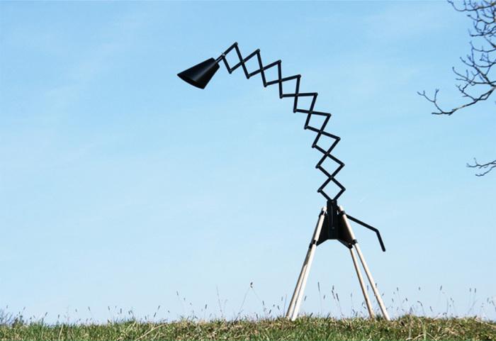 Напольная лампа с необычным креплением абажура, напоминающим жирафа.