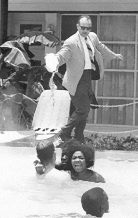 Мужчина выливает кислоту в бассейн, пока в нем купаются темнокожие.