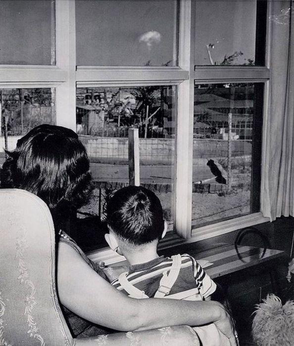 Мать и сын смотрят на облако-гриб после испытания ядерного оружия.