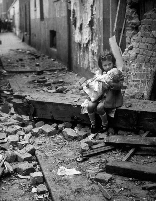 Девочка с куклой на развалинах дома в Лондоне.