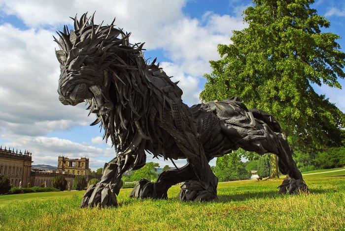 Статуя рычащего льва, сделанная из покрышек.