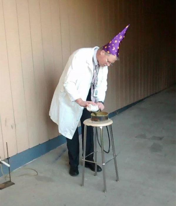 Учитель химии в шляпе волшебника проводит опыты на уроке.