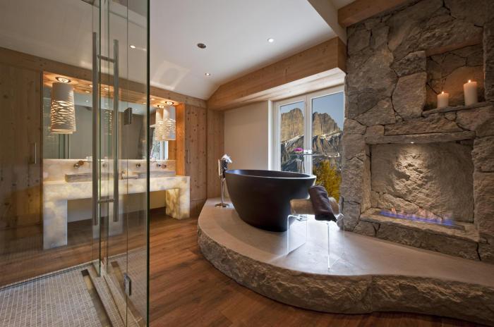 Деревянный пол в сочетании с каменным камином в ванной комнате.