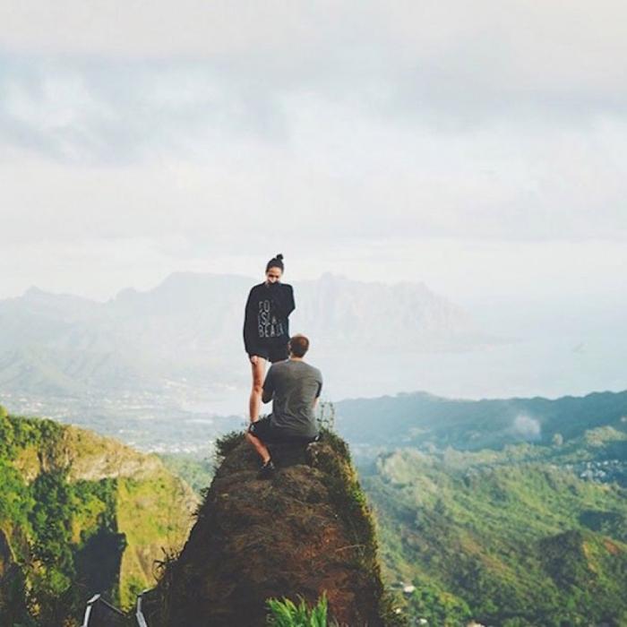 Романтическое предложение руки и сердца на вершине горы во время похода.