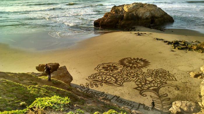 Оригинальное предложение руки и сердца с помощью красивого рисунка на песке.