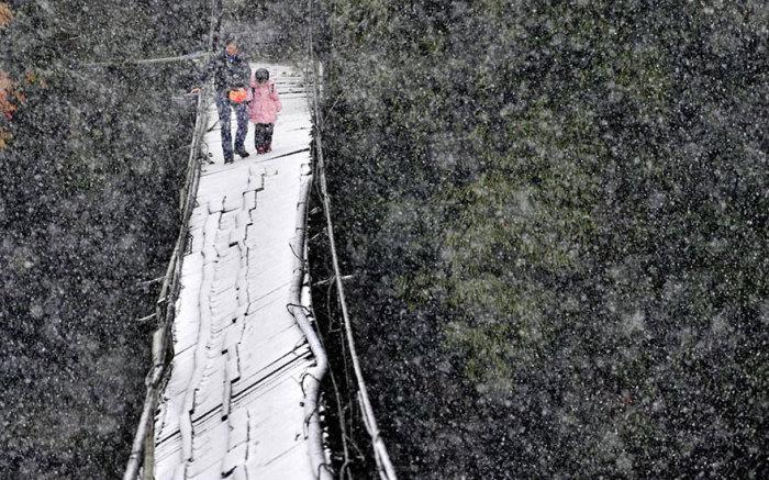 Ребенок идет с мамой в школу через заснеженный мост.