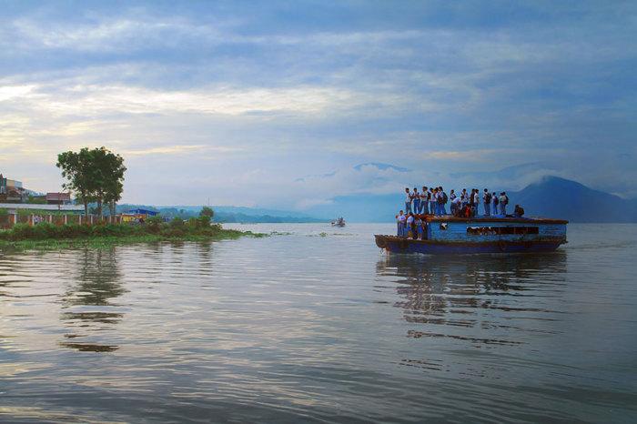 Дети на деревянной лодке по пути в школу в Индонезии.