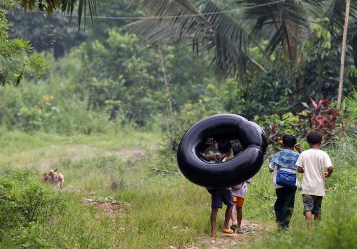 Ученики младшей школы добираются на учебу вплавь на накачанных шинах.