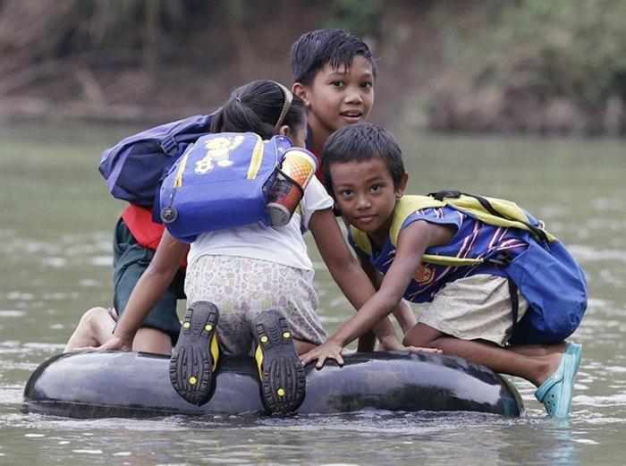 Дети в маленьком городке в Филиппинах добираются в школу вплавь.