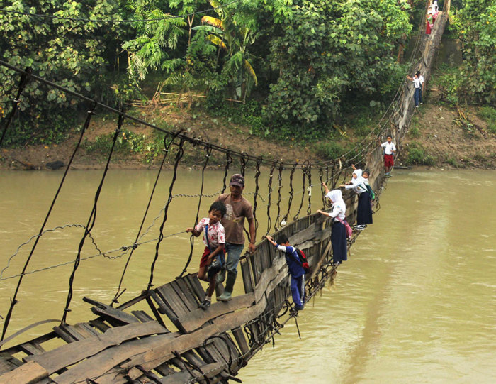 Дети города Лебак добираются в школу по разрушенному подвесному мосту.